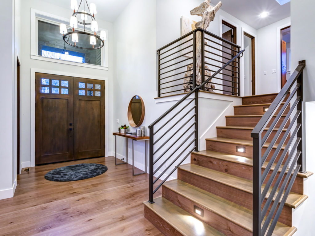 Chic entrance foyer with high ceiling and wide staircase with lights and contemporary railing. New Custom built home interior.