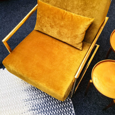 Dark yellow velvet armchair and golden side table. Modern furniture with retro feel.